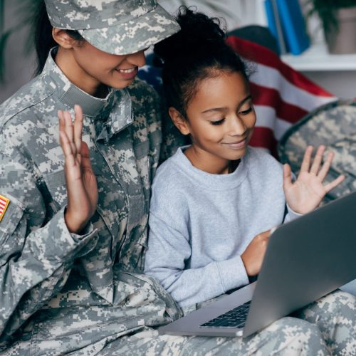 african american soldier in military uniform and child making video call with laptop